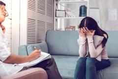 Depressed krossad moloken brunhårig klient som har en terapi med psykologen arkivfoton
