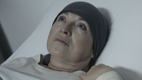 Depressed lady in scarf lying in bed with no hope for recovery, cancer treatment. Stock footage stock video footage