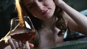 Depressed lady sitting alone in bar, looking at glass of brandy, break up stock video