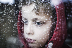 Depressed little boy. Sad boy looking through window at rainy weather. Can't play Stock Photography