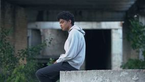Depressed lonely black male sitting abandoned building thinking of problem. Stock footage stock footage