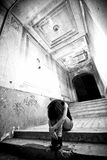 Depressed lonely woman sitting on stairs at abandoned building Royalty Free Stock Image