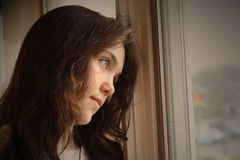 Depressed looking out window. Teen girl depressed looking out window Stock Photo