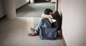 Depressed male student with head on knees. Sitting by wall in college Royalty Free Stock Images