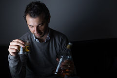 Depressed man abusing of alcohol. Trying to forget his problems Royalty Free Stock Photography