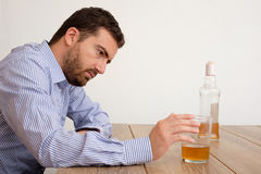 Depressed man abusing of alcohol trying to forget his problems Stock Photos