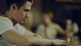 Depressed man in bar. Depressed young man sitting at a bar counter in a bar stock footage