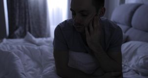 Depressed man in bed suffers from a symptom insomnia. Depressed man in bed suffers from a symptom of insomnia stock video footage