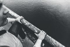 Depressed man climbs over railing of bridge to jump and commit suicide, hopelessness and depression problems concept. Black and white photo Stock Photos