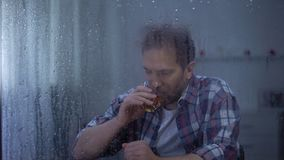 Depressed man drinking whiskey alone on rainy day, thinking about life problems. Stock footage stock video footage