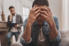 Depressed man feeling horrified clutching his head. Clutching head. Depressed anxious men feeling very horrified clutching his head while visiting psychologist royalty free stock photo