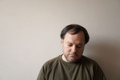 Depressed man in his forties. Leaning against wall with copy space. depression or midlife crisis concept Royalty Free Stock Photo