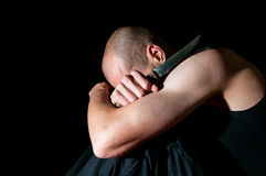 Depressed man with knife and suicidal thoughts. Dark image. Black background royalty free stock image