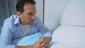 Depressed man looking at empty hospital bed, trying to cope with his grief, loss