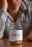 Depressed Man Looking At Empty Jar Labelled Childcare Royalty Free Stock Images