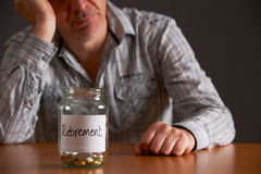 Depressed Man Looking At Empty Jar Labelled Retirement Royalty Free Stock Photos