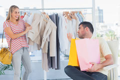 Depressed man looking at his shopaholic girlfriend Stock Photo