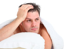 Depressed man lying in bed. Depressed young man lying in bed on white background Stock Photo