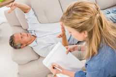 Depressed man lying on couch and talking to therapist Stock Photography