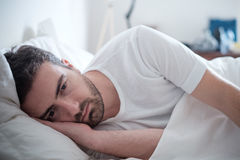 Depressed man lying in his bed and feeling bad Stock Image