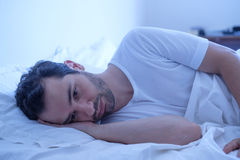 Depressed man lying in his bed and feeling worried Royalty Free Stock Photo