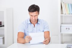 Depressed Man Reading Paper stock images