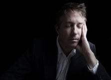 Depressed man resting his eyes. Portrait of businessman closing eyes while working late at night on black background with copy space Royalty Free Stock Photography