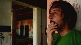 Depressed man in ruined interior as a metaphor for his internal dilemmas and emotions.