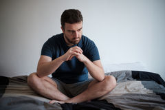 Depressed man seated on his bed Royalty Free Stock Image
