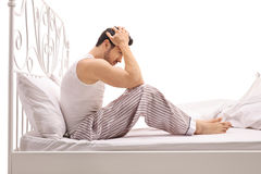 Depressed man sitting on a bed with his head down Royalty Free Stock Photo