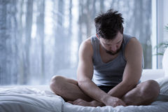 Depressed man sitting on bed Royalty Free Stock Photos