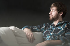Depressed man is sitting on couch Royalty Free Stock Photo