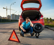 Depressed man sitting near car with punctured tire. Sad and depressed man sitting near car with punctured tire royalty free stock photo