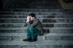 Depressed man sitting out side on steps feeling tired and sad. Latin man stressed from work sitting on steps outside feeling anxiety in adult cause of Royalty Free Stock Photos