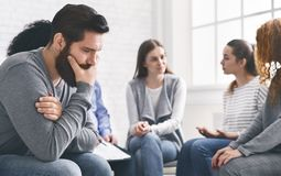 Depressed man sitting at rehab group therapy. Psychotherapy, depression, life issues concept. Depressed men sitting at rehab group therapy and thinking about his stock photo