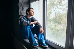 Depressed man sitting on the window sill, psycho. Depressed man sitting on the window sill in dark room, psycho patient. Mentally ill people concept, stressed Royalty Free Stock Photos