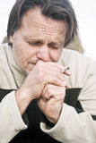 Depressed man smoking cigarette Stock Images