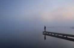 Depressed. Man standing at the end of a jetty on a foggy day Stock Photography