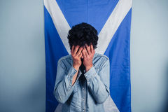 Depressed man standing in front of scottish flag Stock Photography
