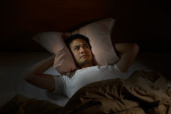 Depressed man suffering from insomnia. Lying in bed Royalty Free Stock Photography
