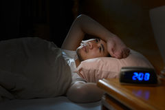 Depressed man suffering from insomnia. Lying in bed Stock Photography