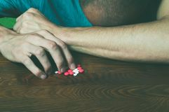 Depressed man suffering from suicidal depression want to commit suicide by taking strong medicament drugs and pills. Royalty Free Stock Image