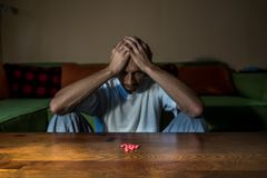 Depressed man suffering from suicidal depression want to commit suicide by taking strong medicament drugs and pills stock images