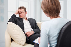 Depressed man talking with psychologist Royalty Free Stock Photography