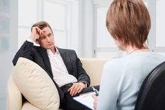 Depressed man talking with psychologist Royalty Free Stock Images