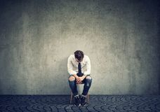Sorrowful lonely man on chair. Depressed man upset with bad luck sitting on chair alone against gray background stock image