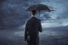 Depressed manager standing with an umbrella Royalty Free Stock Image