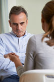 Depressed Mature Man Talking To Counsellor Royalty Free Stock Photography