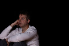 Depressed mature man thinking in dark background Royalty Free Stock Photos