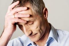 Depressed mature man. Touching his head Royalty Free Stock Photos